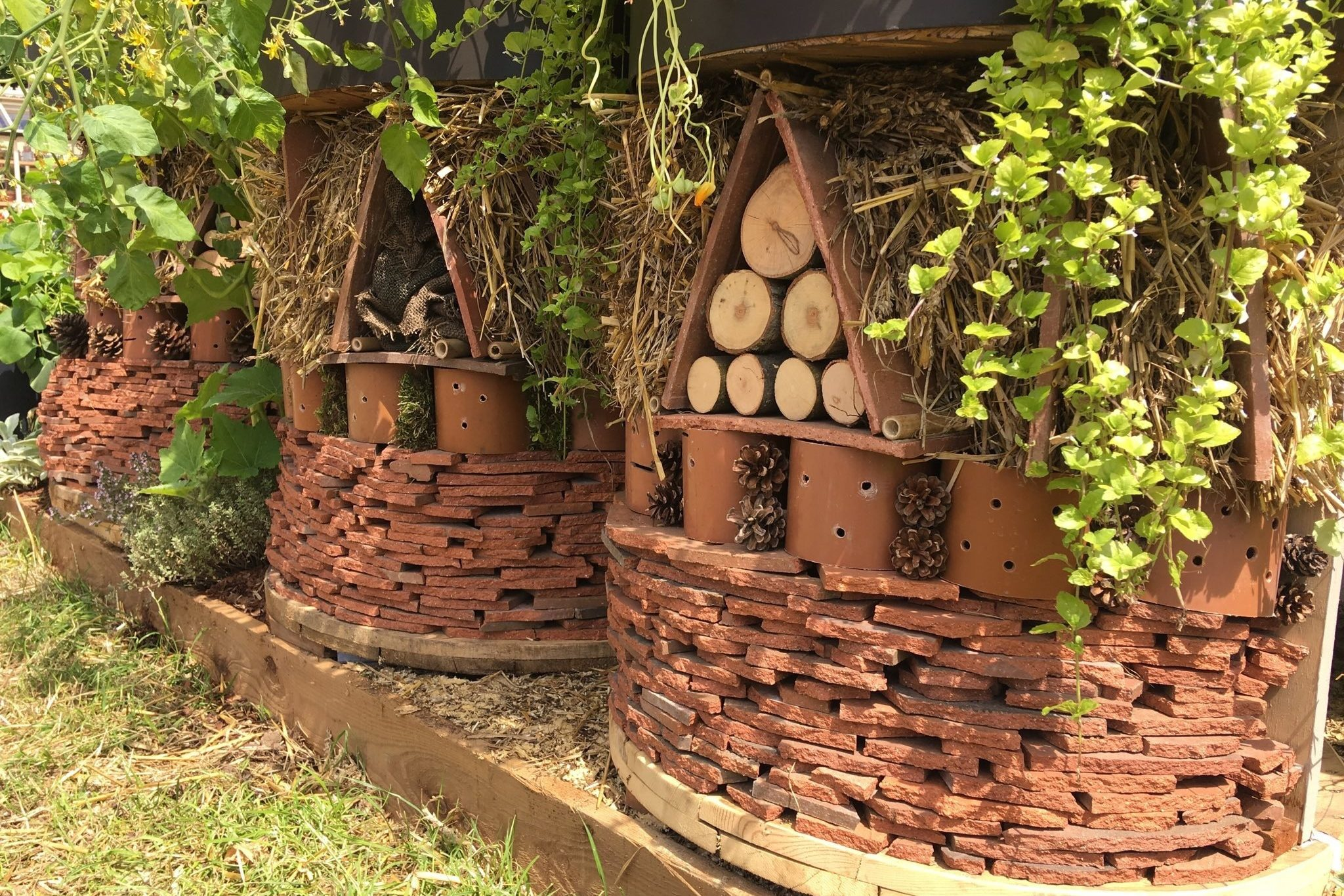 Raised planters incorporate bug hotels made from tiles and wood