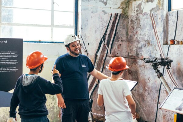 Two young people wearing hard hats talk to a guide at Geevor mine whilst looking at a wall of rock