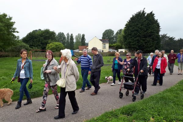 Group of older people walking on a path together and chatting
