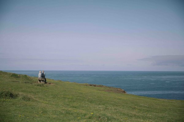 A distant view of a couple sitting on a bench looking out to sea