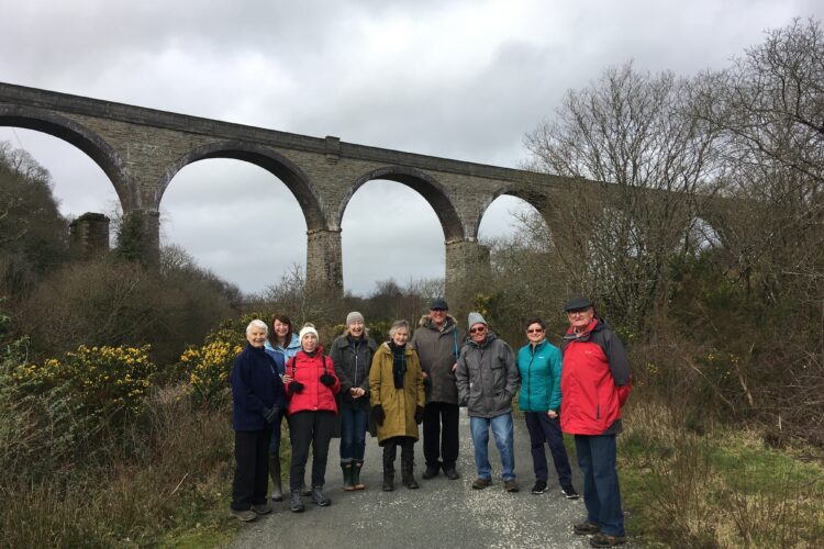A walking group standing in front of a tall viaduct