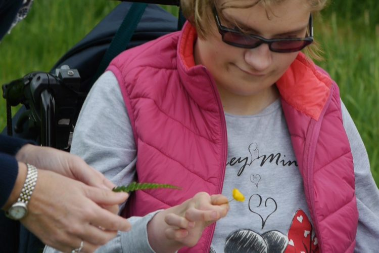 A young woman exploring the detail of a buttercup flower