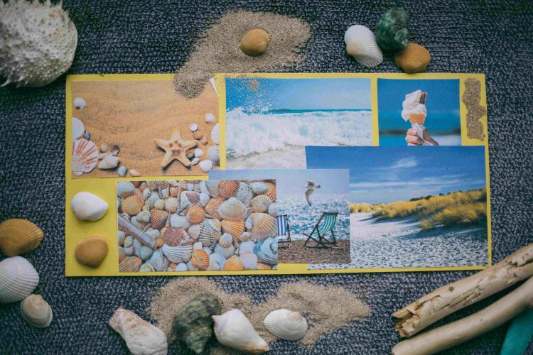 A handmade postcard with images of the beach and sea. The postcard is surrounded by sand, shells and driftwood