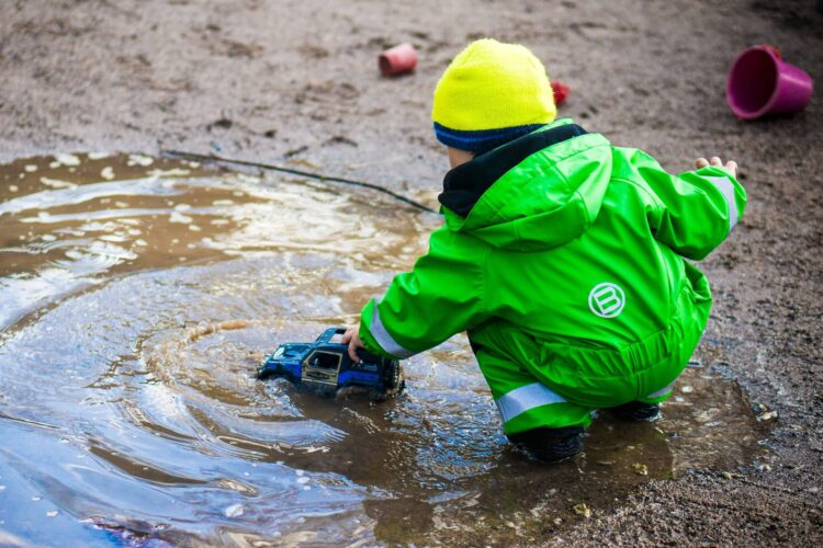 Young child having fun with a puddle