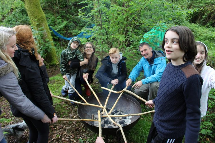 A family gather around a fire to cook bread as part of a Sensory Trust activity day