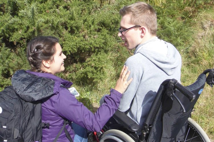 Boy in wheelchair takes part in a sensory story outside