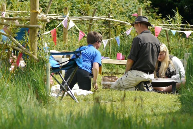 Families play together on the grass at one of the Sensory Trust Nature activity days