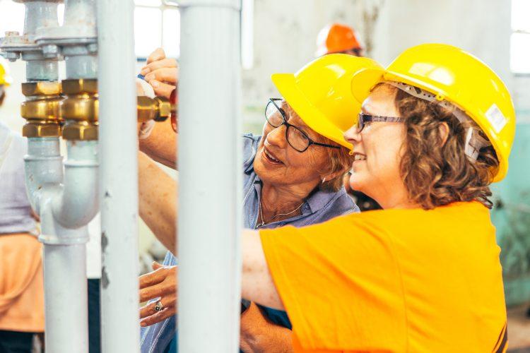 Two women in hard hats explore the workings of Geevor mine