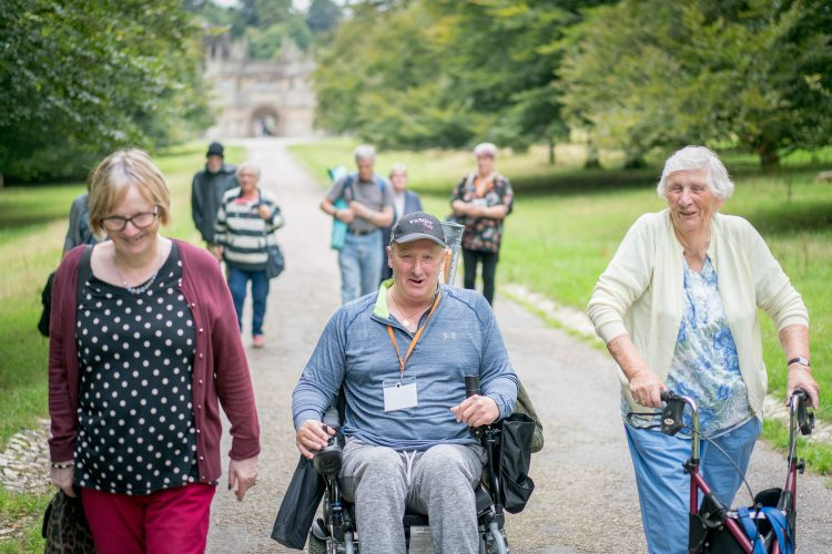 A group of older people and a man in a wheelchair walking at a National Trust property