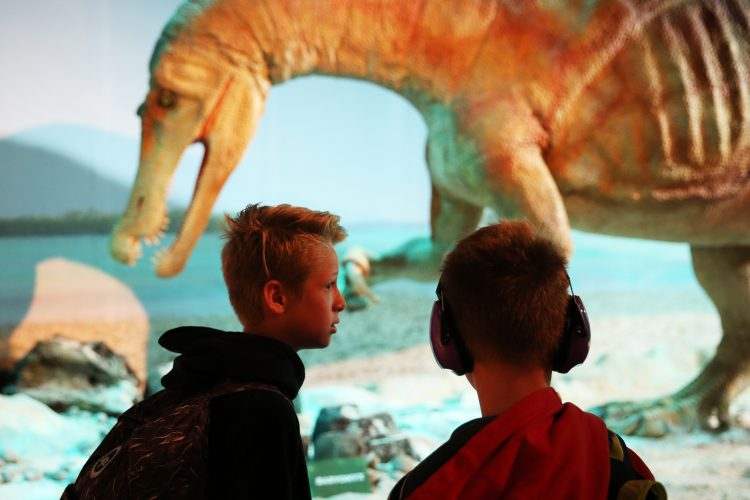 Young people with a dinosaur as par of a relaxed session at Eden Project