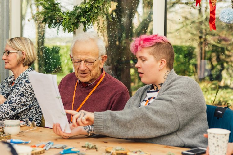 Dementia friendly group participate in a singing activity and sing from words on a sheet