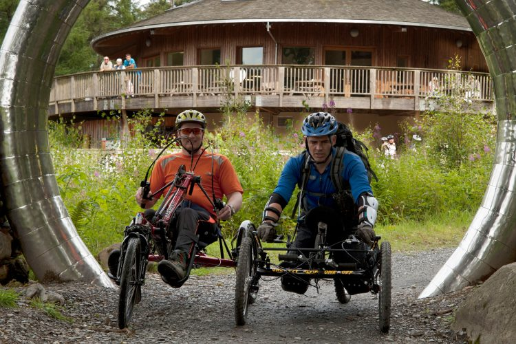 Two cyclists using wheelchair-adapted bikes