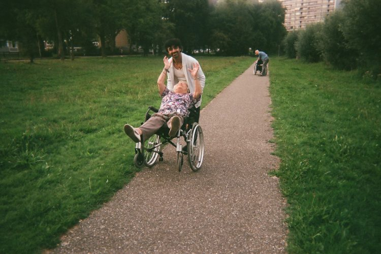 Lady in a wheelchair laughing with her hands in the air as she is being pushed along on two wheels