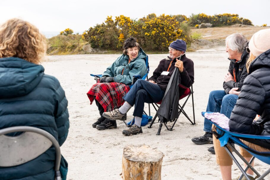 Participants of a dementia friendly walking group gather on camping chairs to talk