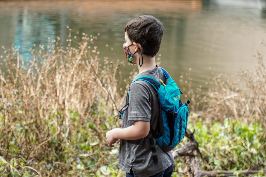 Boy in blue and black backpack standing near a body of water in daytime