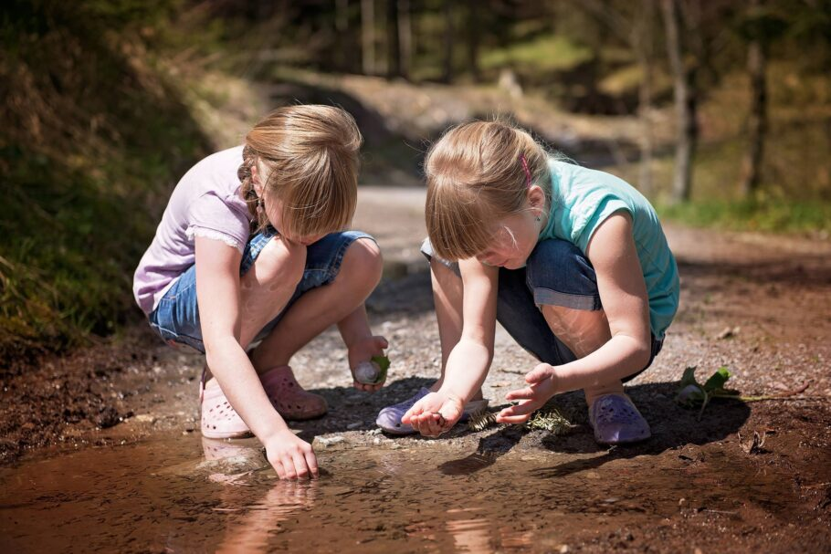 Two girls exploring a puddle