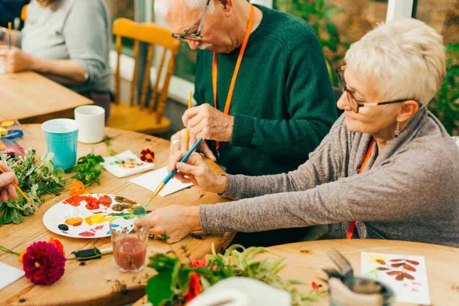 Two older taking part in a painting activity at Potager gardens