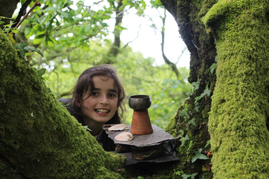 A girl looking through mossy branches of a tree