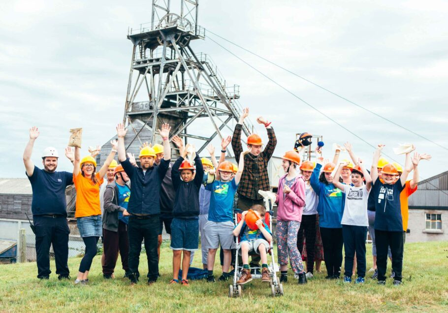 Young people with disabilities gather at Geevor Tin mine with their hands in the air